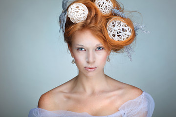Redheaded girl with new-year decorations in a hair-do.