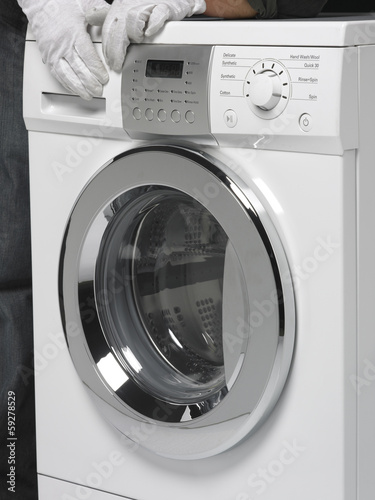 Two hands pushing a Washing machine