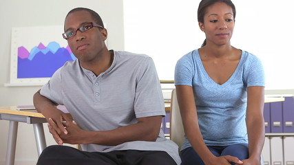 African American office worker whispering to colleague