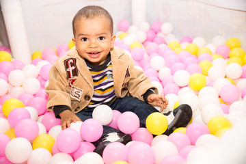 Happy black boy in colored ball on birthday on playground