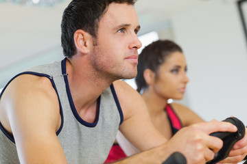 Yyoung man and woman working out at spinning class