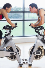 Side view of a woman and man working out at spinning class