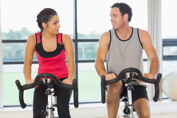 Man and woman working out at spinning class