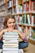 Happy student sitting on library floor leaning on pile of books