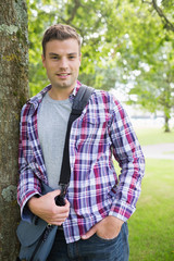 Handsome student leaning on tree looking at camera