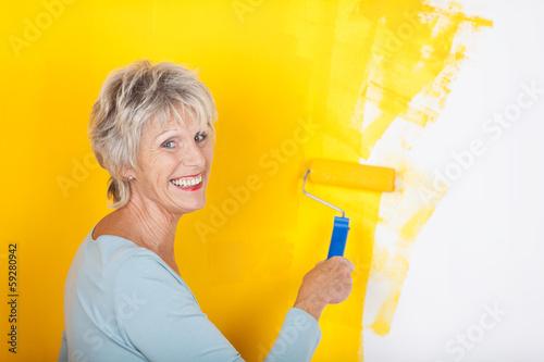 lachende seniorin streicht ihre wohnung