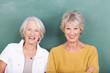 zwei ältere freundinnen vor einer schultafel