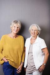zwei seniorinnen stehen vor grauer wand