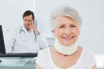 Senior patient in surgical collar with doctor at office