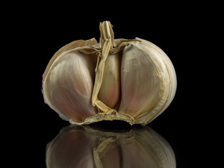 garlic head on a black background with reflection