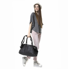 casual young woman in cap with a black bag walking