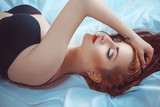 Sensual red hair woman lying in bed