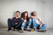 Skateboarder friends portrait sit against concrete wall.