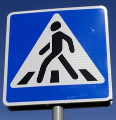 """Дорожный знак """"Пешеходный переход"""" на фоне синего неба"""