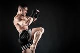 Fototapeta Sportsman kick boxer fighting against black background.