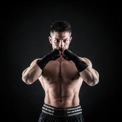 Sportsman kick boxer intense portrait against black background.