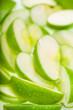 Green wet apple slices. Food background