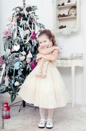 child with a toy hare near a Christmas fir-tree