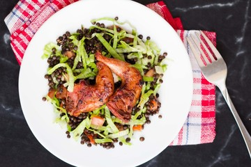 Delicious salad with black lentils, fried legs quail, tomatoes