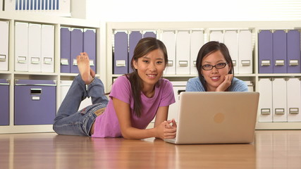 Cute Asian college girls lying on floor