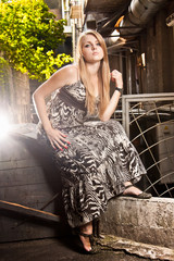 Sexy blond woman in long dress sitting at old courtyard