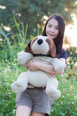 Thai Woman Hug Stuffed dog on in Grass