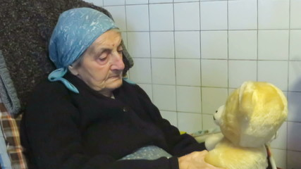 Senior woman sitting with a fluffy toy