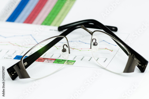 Broken black glasses on business graph