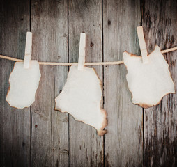 old burnt paper attach to rope with clothes pins on wooden backg