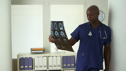 African American medical professional reviewing brain scans