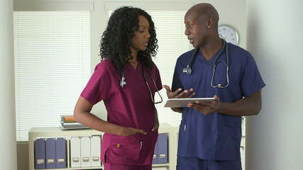 African American doctors talking together with tablet pc