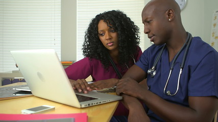 Medical team working together on laptop computer
