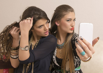 Portrait of two girls taking photos with cell phone