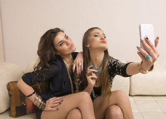 Portrait of two girls taking photos with cellphone