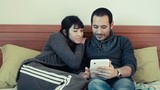 couple using tablet on the bed at home