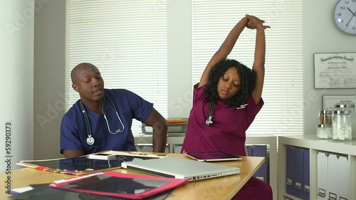 Tired medical doctors yawning and stretching at desk