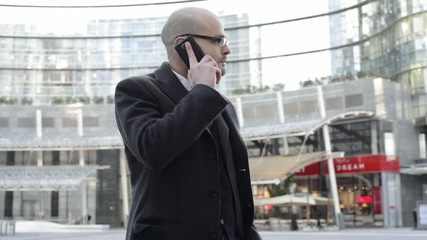 elegant handsome businessman on the phone in business district