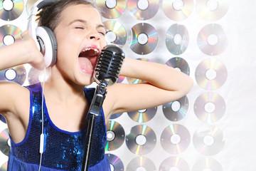 Dziewczynka w niebieskiej sukience śpiewa karaoke