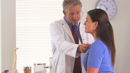Doctor listening to elderly woman's heartbeat