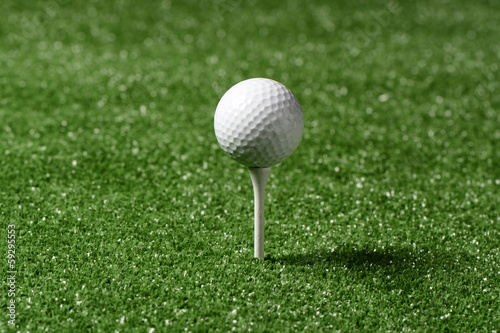 Pelota de golf y tee en césped artificial