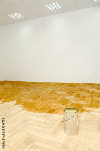 Home or office renovation varnished oak parquet floor and can