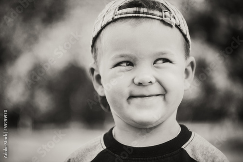 Happy child wearing striped cap in outdoor portrait
