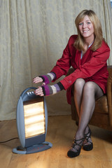 Woman using a portable electric room heater