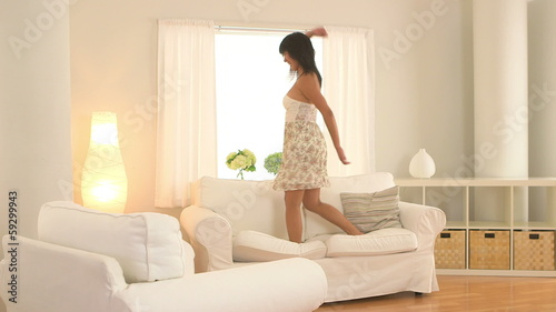 Taiwanese woman jumping on couch and dancing in living room