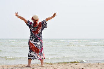 Happy mature woman enjoying breeze on seashore