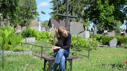 Widow woman near soldier lover grave. Lithuania national flag
