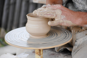 Craftsman making vase from fresh wet clay on pottery wheel