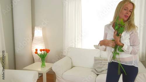 Mature woman dancing with bouquet of flowers in living room