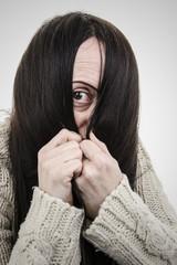 Shy, woman hiding face behind hair