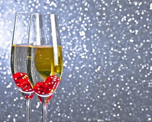 red dice dropping in the champagne flutes on bokeh background